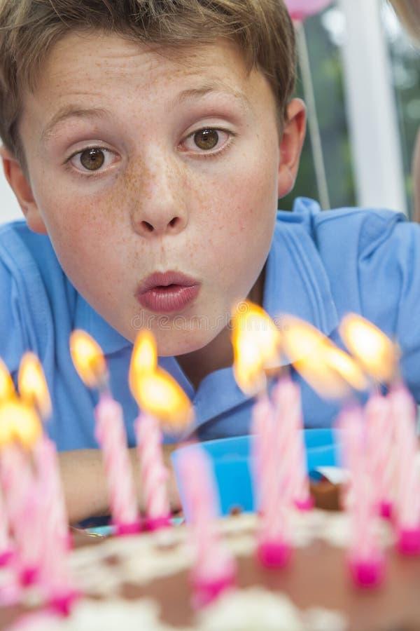 Het Kind dat van de jongen uit de Kaarsen van de Cake van de Verjaardag blaast royalty-vrije stock foto