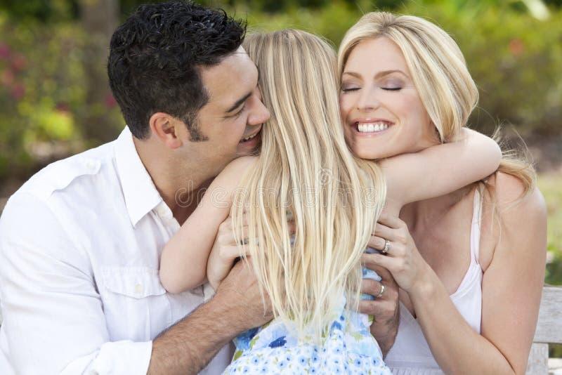 Het Kind dat van het meisje Gelukkige Ouders in Park of Tuin koestert royalty-vrije stock afbeelding