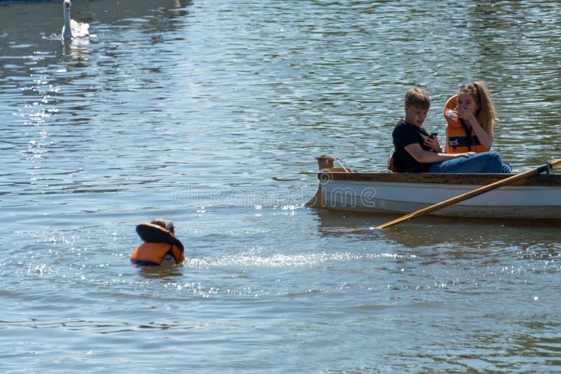 Het kind die buoancyhulp dragen valt in water met vriend doen schrikken en geschokt kijken royalty-vrije stock foto's