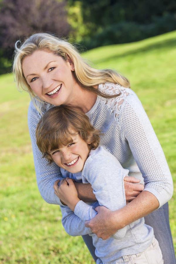 Het Kind die van de de Vrouwenjongen van de moederzoon buiten in Zonneschijn lachen royalty-vrije stock fotografie