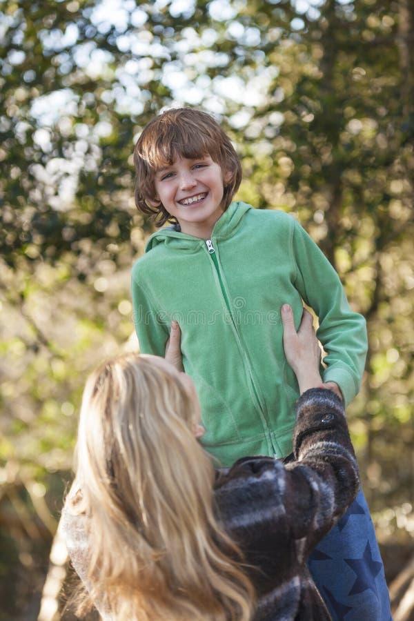 Het Kind die van de de Vrouwenjongen van de moederzoon buiten in Zonneschijn lachen royalty-vrije stock foto