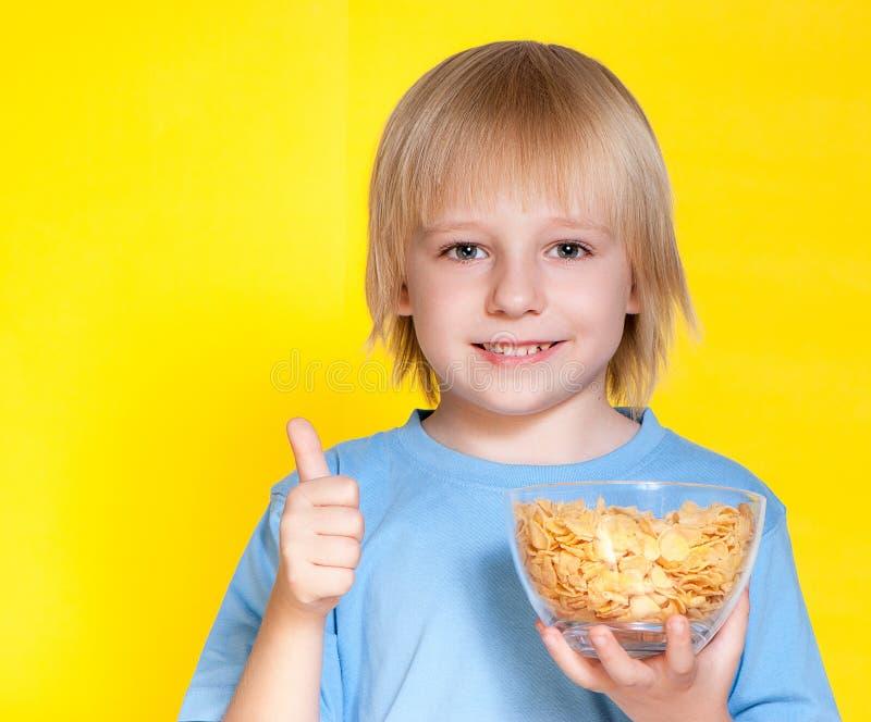 Het kind die van het jongensjonge geitje cornflakesgraangewas eten stock foto