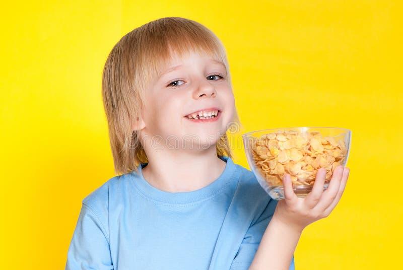 Het kind die van het jongensjonge geitje cornflakesgraangewas eten royalty-vrije stock afbeelding