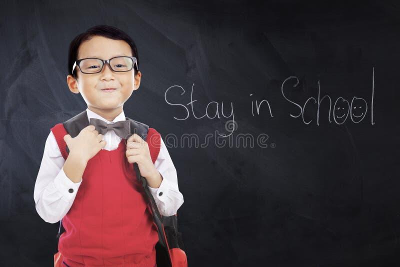 Het kind draagt eenvormig met tekstverblijf in School stock afbeeldingen