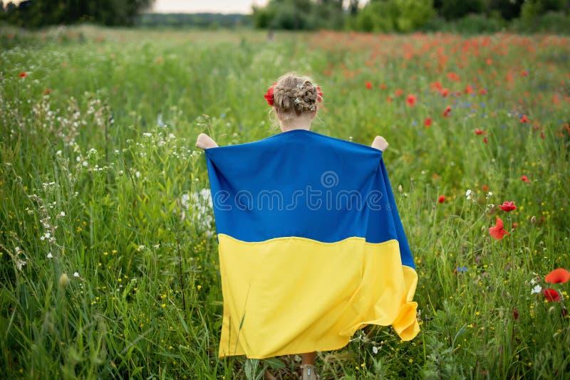 Het kind draagt fladderende blauwe en gele vlag van de Oekra?ne op gebied De Onafhankelijkheidsdag van de Oekra?ne ` s De Dag van royalty-vrije stock foto