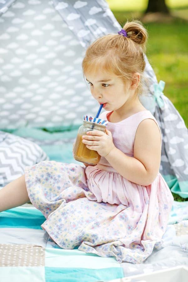 Het kind drinkt een smoothie in het park Het concept is gezond stock foto's