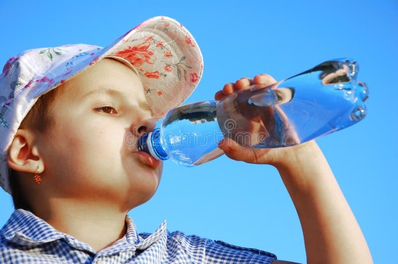 Het kind drinkt mineraalwater stock afbeeldingen