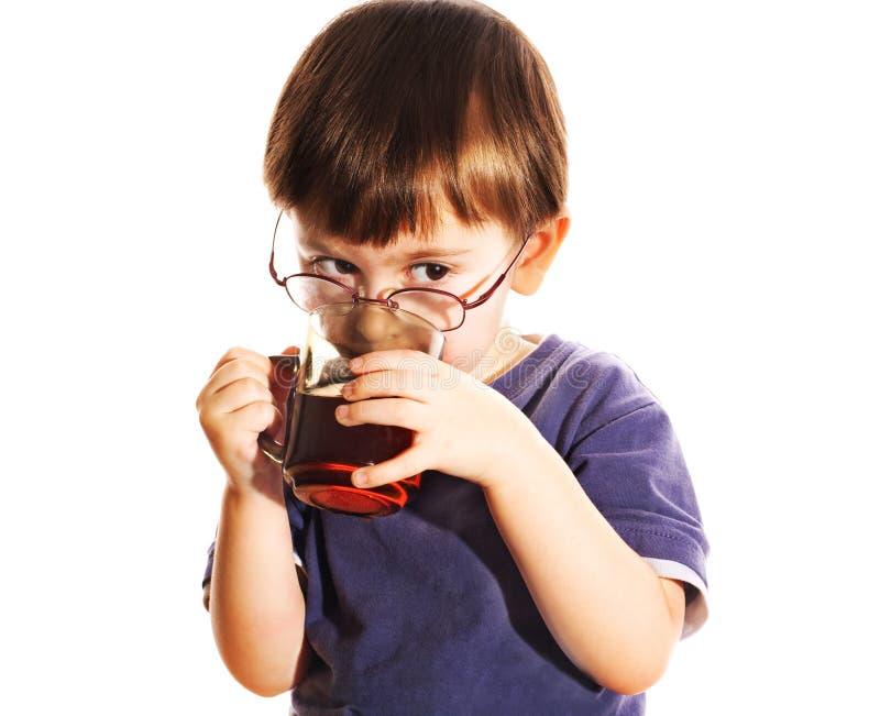Het kind drinkt wat thee stock afbeelding
