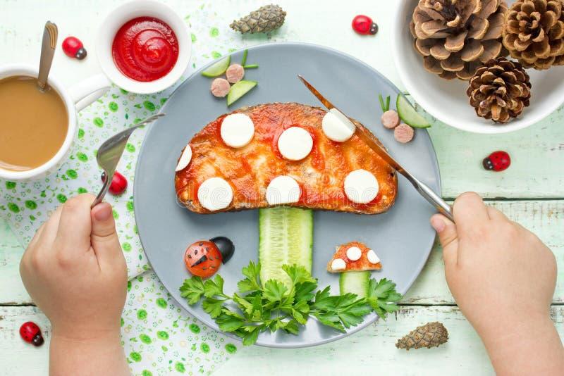 Het kind eet grappige brunch van toost met tomatensaus, kaas en stock foto