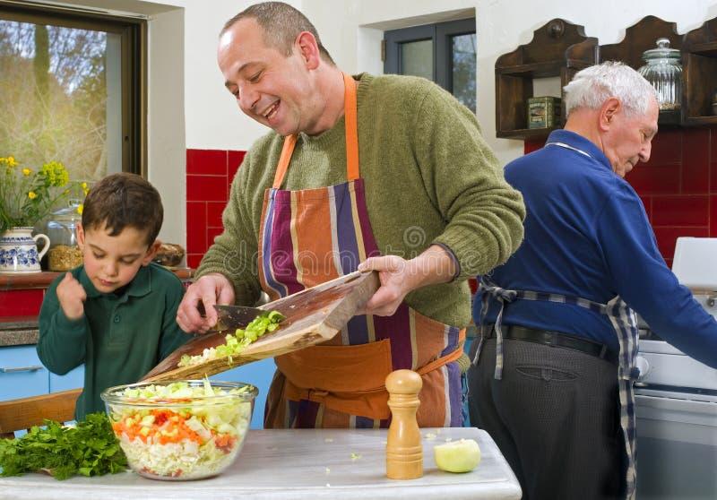 Het kind en de grootvader het koken van de vader stock afbeelding