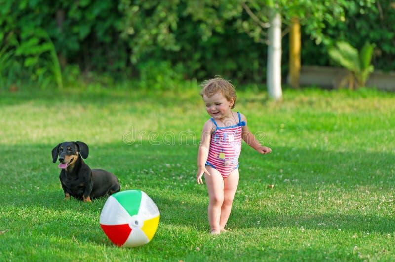 Het kind en de hond spelen in een gras royalty-vrije stock afbeelding