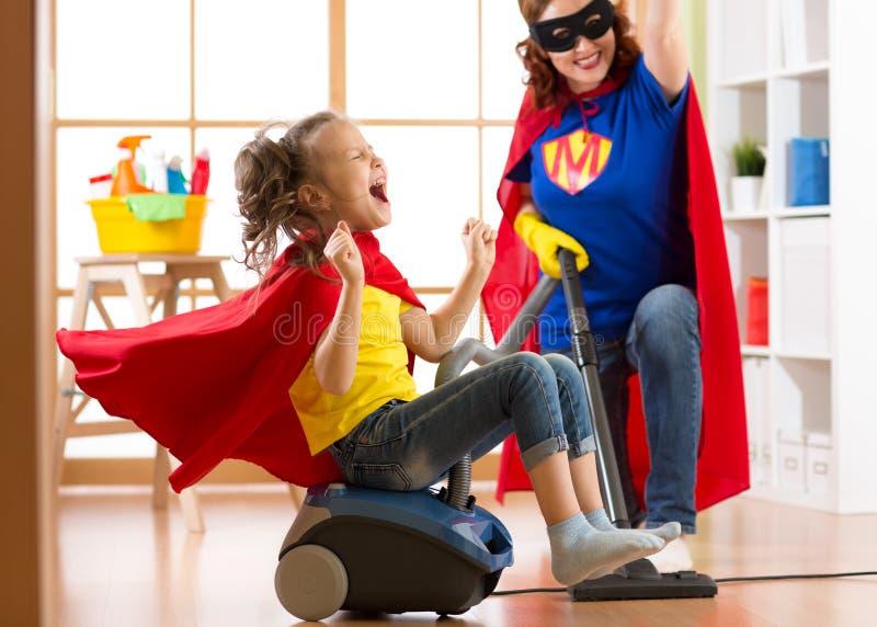 Het kind en de moeder kleedden zich als superheroes het gebruiken van stofzuiger in ruimte Hebben de de familievrouw en dochter o stock fotografie