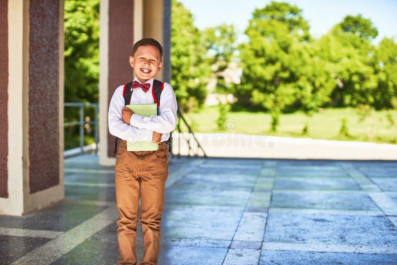 Het kind gaat naar lage school portret van een gelukkig kind met een aktentas op zijn rug royalty-vrije stock afbeeldingen
