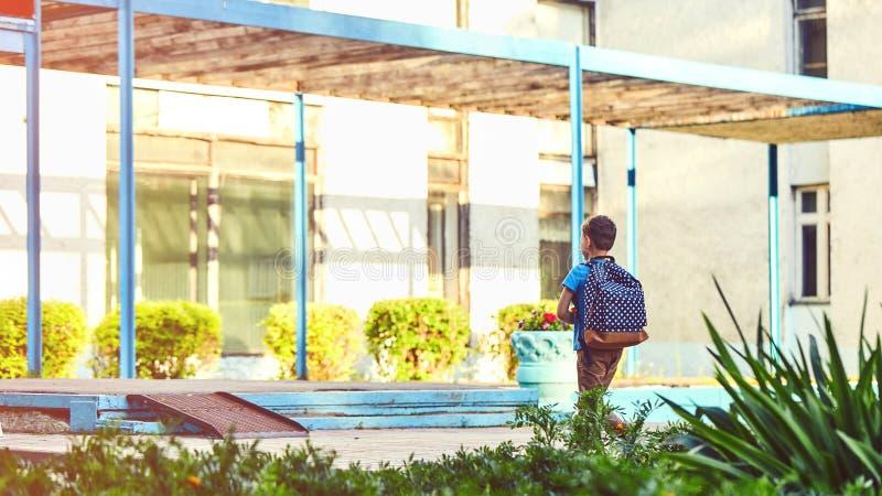 Het kind gaat naar school de jongensschooljongen gaat naar school in de ochtend gelukkig kind met een binnen aktentas op zijn rug royalty-vrije stock foto