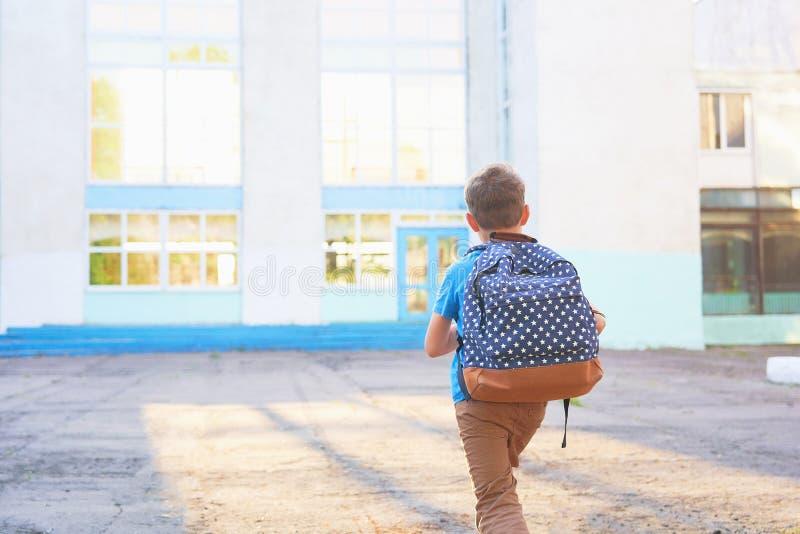 Het kind gaat naar school de jongensschooljongen gaat naar school in de ochtend gelukkig kind met een binnen aktentas op zijn rug stock foto's