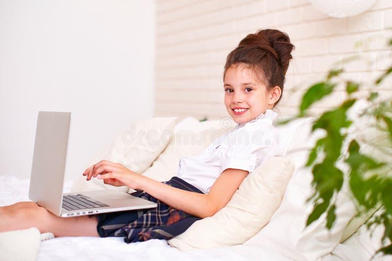 Het kind is gelukkig om met vrienden via Internet te communiceren huis het scholen, onderzoek en studie, nieuwe kennis gelukkige  stock foto