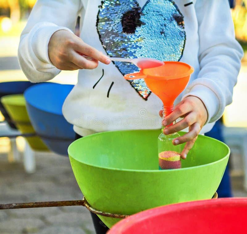 Het kind giet gekleurd zand in de fles stock foto