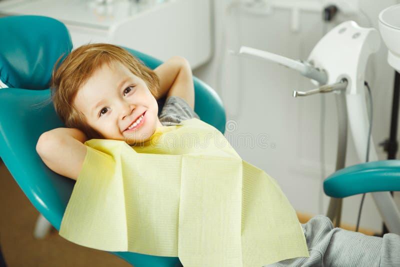 Het kind in goede stemmingszitting op stoel en zonder jongen van Young van de vrees de wachtende tandarts gaat tanden behandelen  royalty-vrije stock foto's