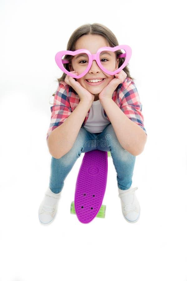 Het kind in hart gevormde oogglazen houdt van met een skateboard rijdend Blij en gelukkig Geniet van de toevallige stijl van het  stock afbeeldingen