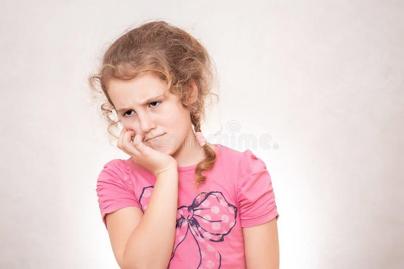 Het kind heeft een pijnlijk oor Meisje die aan otitis lijden Het jonge meisje heeft een tandpijn, gelaatsuitdrukkingconcept royalty-vrije stock foto