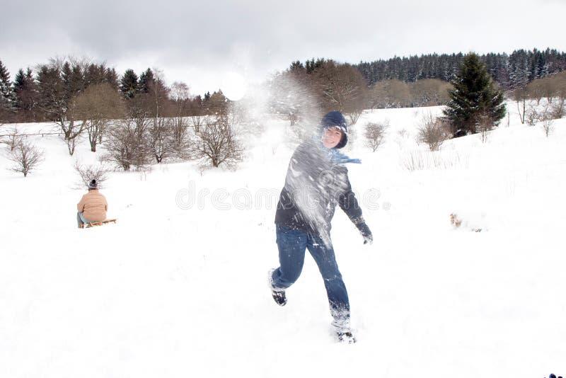 Het kind heeft een sneeuwbalstrijd in wit stock afbeelding