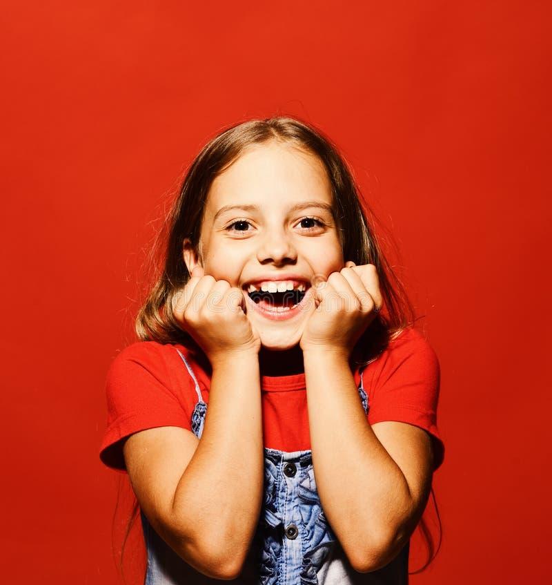 Het kind heft haar wangen in opwinding op Meisje met glimlach stock afbeelding