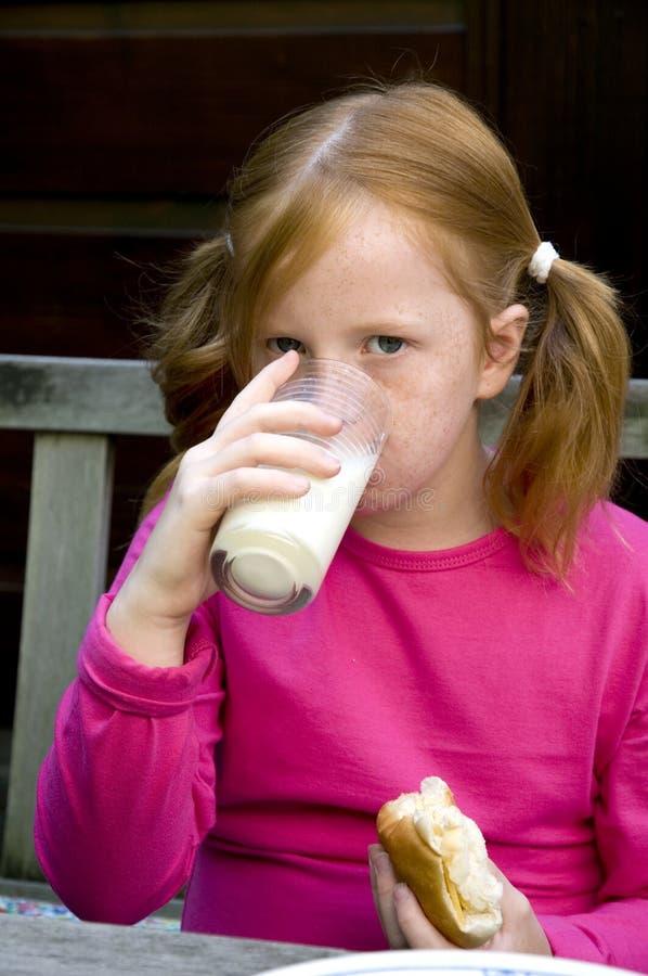 Het kind is het drinken melk stock afbeeldingen