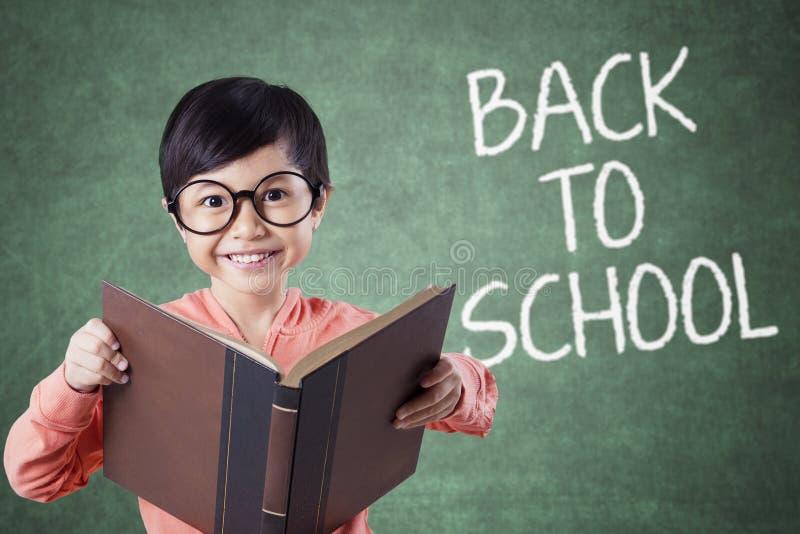 Het kind houdt boek met terug naar schooltekst in klasse stock afbeeldingen