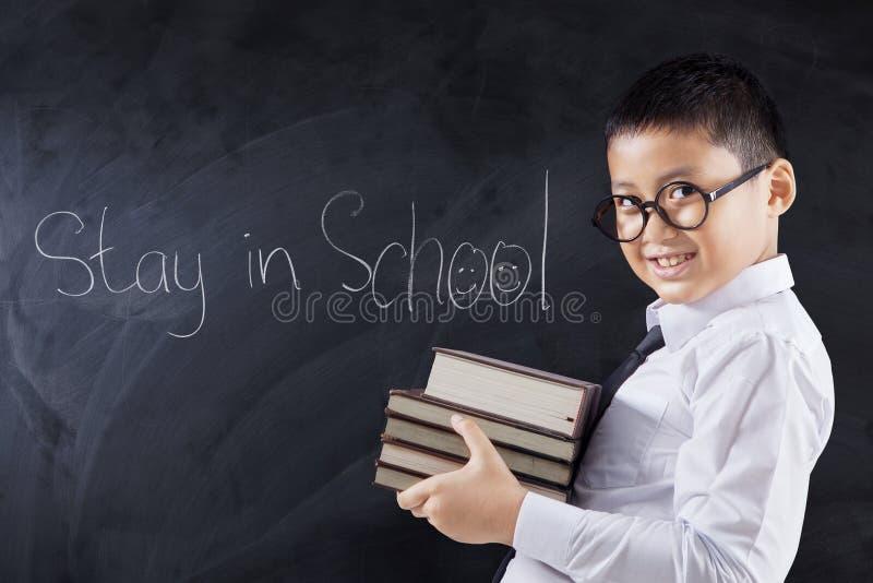 Het kind houdt boeken met tekstverblijf in School stock fotografie