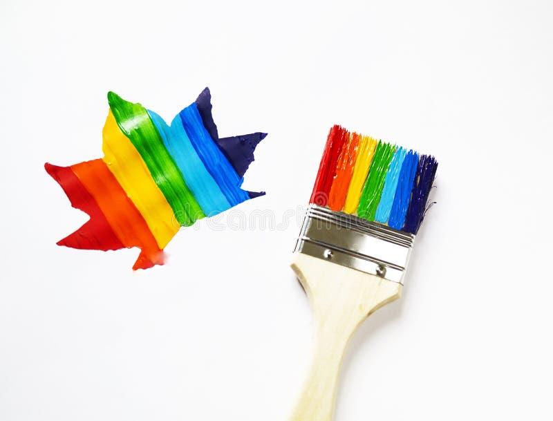 Het kind houdt de borstel Het jonge geitje schildert een esdoornblad in alle kleuren van de regenboog wordt geschilderd die Multi stock foto's