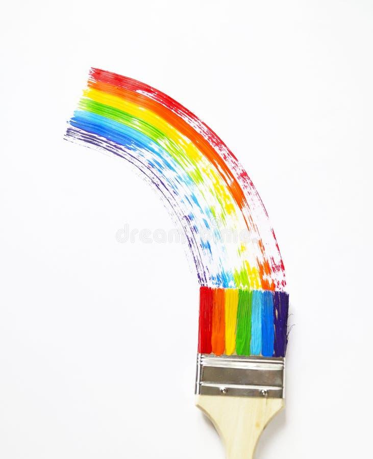 Het kind houdt de borstel Het jonge geitje schildert een esdoornblad in alle kleuren van de regenboog wordt geschilderd die Multi royalty-vrije stock fotografie