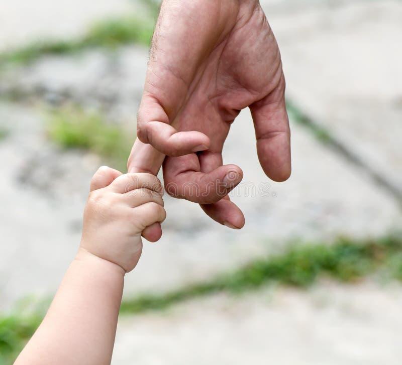 Het kind houdt de vinger van een hand van de vader stock foto's