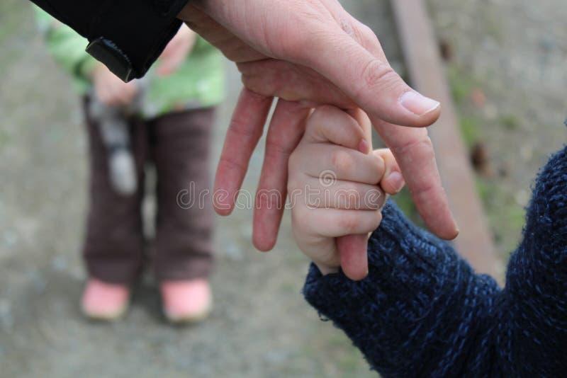 Het kind houdt de vinger van de hand van de vader tegen de achtergrond van de broer of de zuster van een ander kind stock foto's