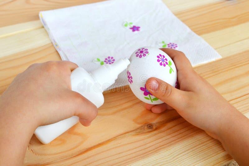 Het kind houdt een een decoupagepaasei en lijm in handen Het kind lijmt de bloemfragmenten van servet aan het ei Pasen-decoupage stock foto