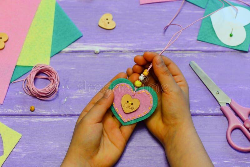 Het kind houdt een gevoelde harthalsband in zijn handen Het kind toont een gevoelde harthalsband Het kind maakte een gift voor mo royalty-vrije stock afbeelding