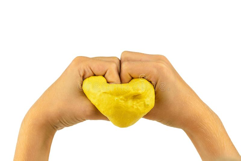 Het kind houdt een hart van geel die slijm op een witte achtergrond wordt geïsoleerd stock afbeeldingen