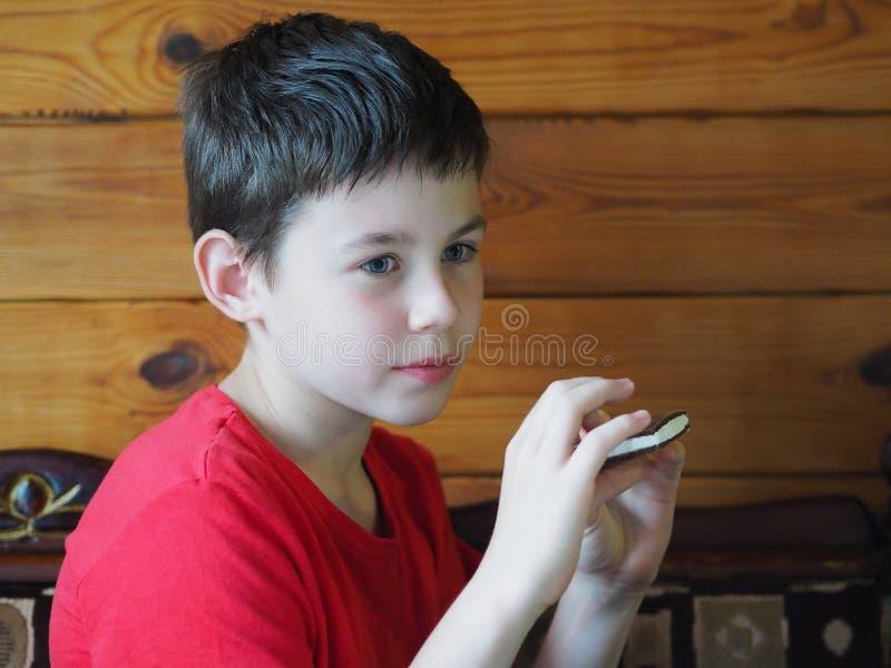 Het kind houdt een koekje in zijn hand stock afbeelding