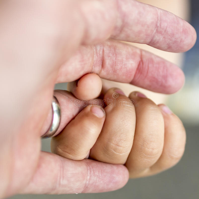 Het kind houdt een ringfinger van zijn vader stock afbeelding