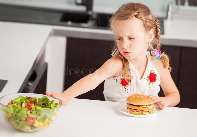Het kind kiest tussen een gezond en ongezond voedsel stock afbeeldingen