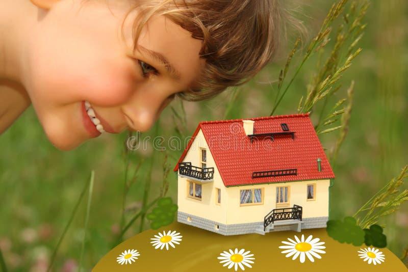 Het kind kijkt openlucht op model van huis royalty-vrije stock foto