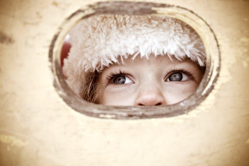 Het kind kijkt uit gat royalty-vrije stock fotografie