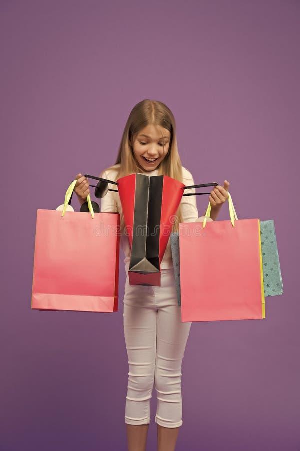 Het kind kijkt in het winkelen zakken op violette achtergrond Weinig shopaholic die glimlach met document zakken wordt verrast Ki stock afbeeldingen