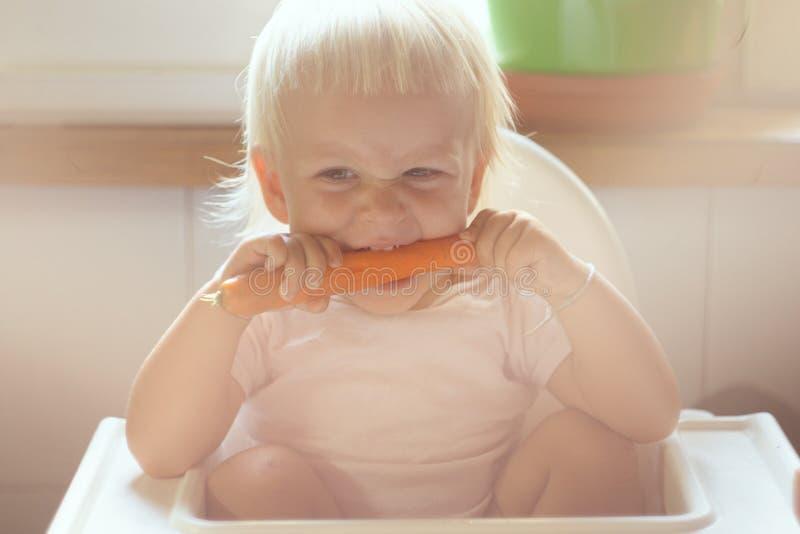 Het kind knaagt aan wortel royalty-vrije stock afbeeldingen