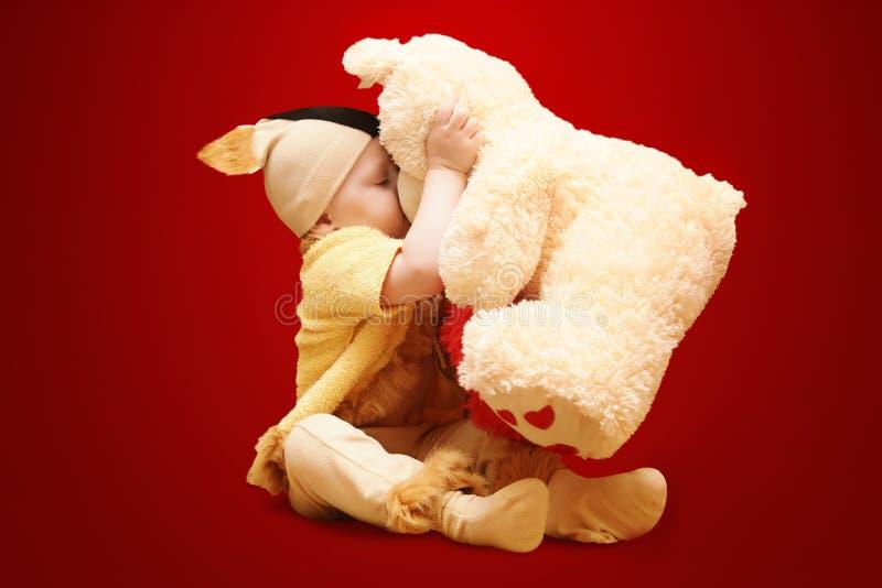 Het kind kust teddybeer royalty-vrije stock fotografie