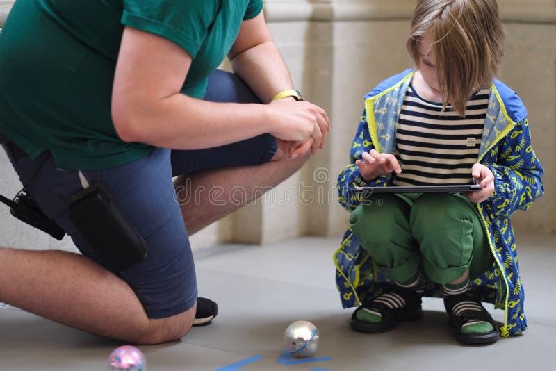 Het kind leert om de robot te controleren stock afbeelding