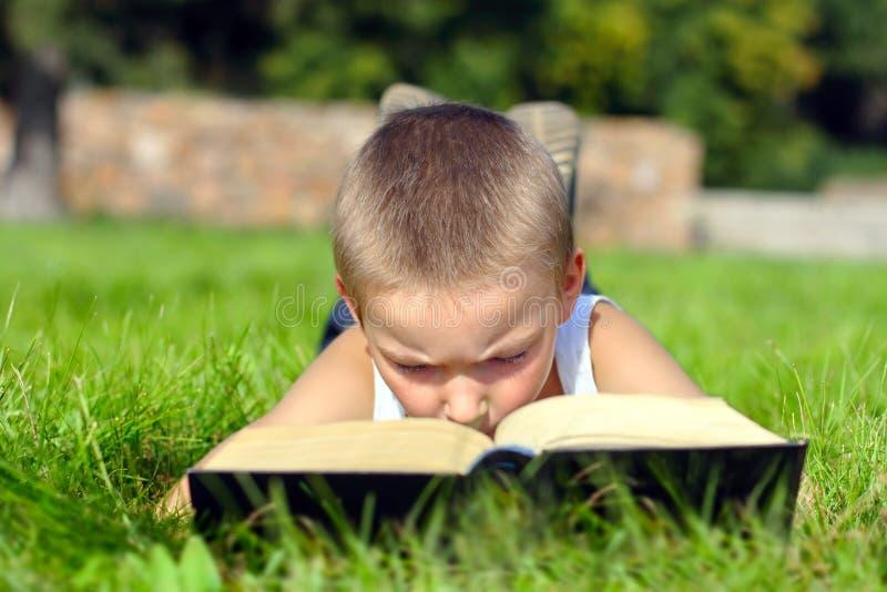 Het kind leest boek stock afbeelding