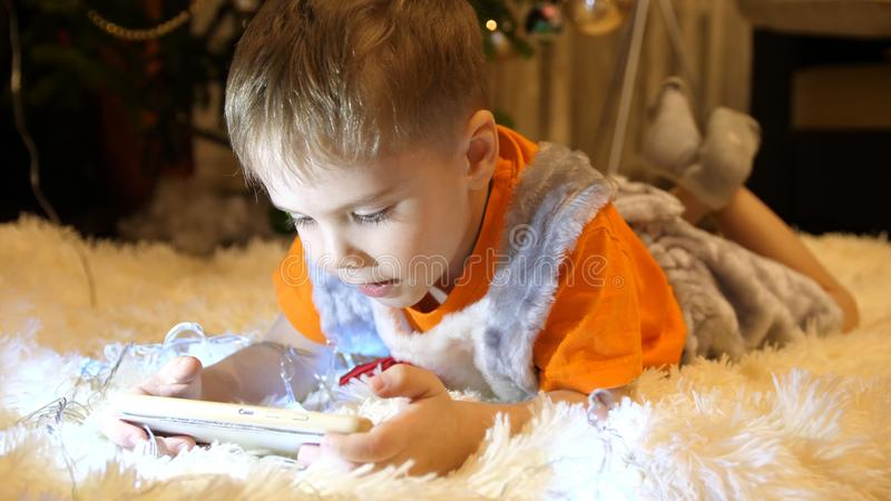Het kind ligt op een zachte witte deken in de ruimte van de kinderen Hij let op beeldverhalen op smartphone Kerstmis stock fotografie