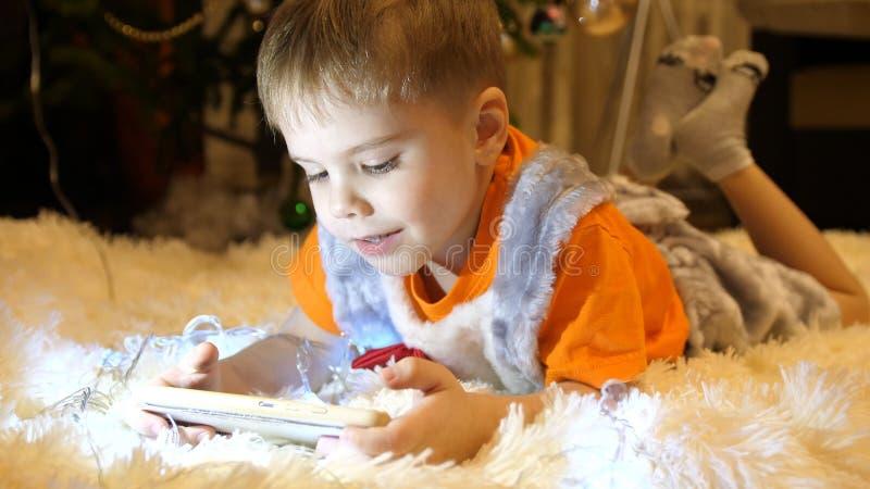 Het kind ligt op een zachte witte deken in de ruimte van de kinderen Hij let op beeldverhalen op smartphone Kerstmis royalty-vrije stock fotografie