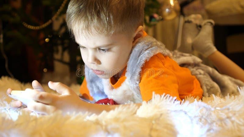 Het kind ligt op een zachte witte deken in de ruimte van de kinderen Hij let op beeldverhalen op smartphone Kerstmis stock afbeelding