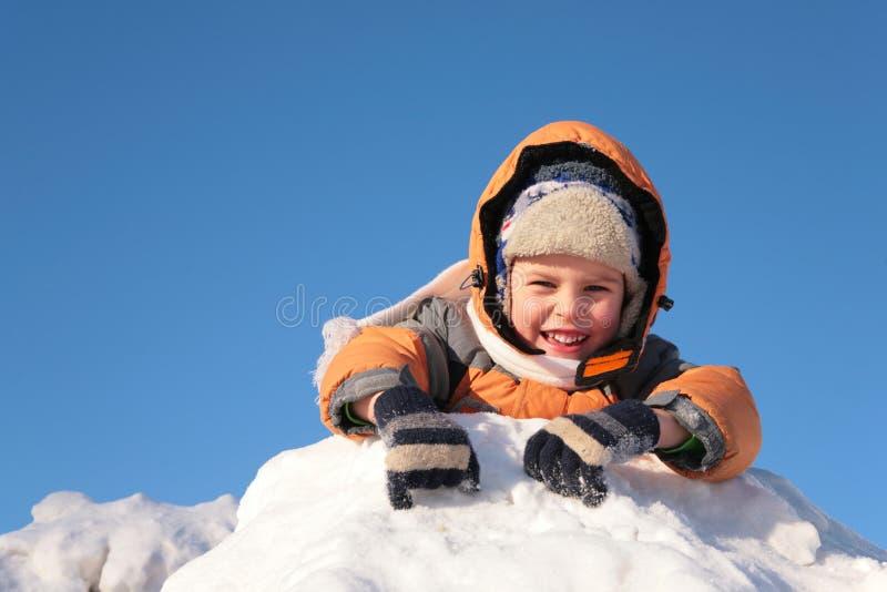 Het kind ligt op sneeuwheuvel royalty-vrije stock fotografie